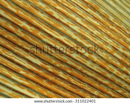 Yellow and orange varicoloured material in diagonal relief stripes - stock photo