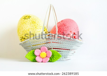 Yellow and pink Easter eggs in a basket with pink flower on white background - stock photo