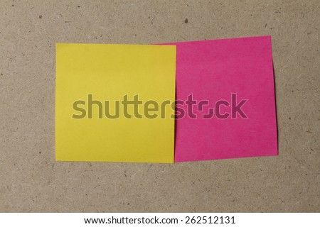 yellow and pink sticky note on brown wall - stock photo