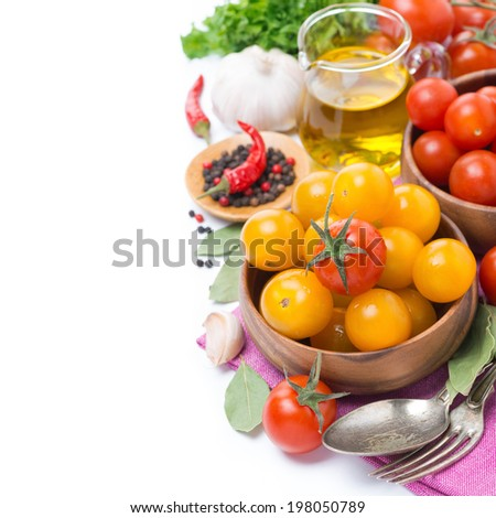 yellow and red cherry tomatoes in bowl, olive oil and spices, isolated on white