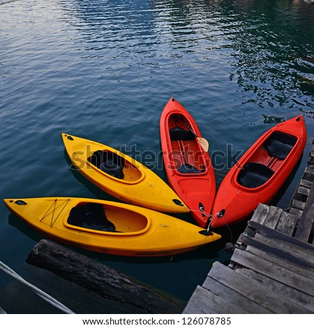 Yellow and Red Kayak on the lake - stock photo