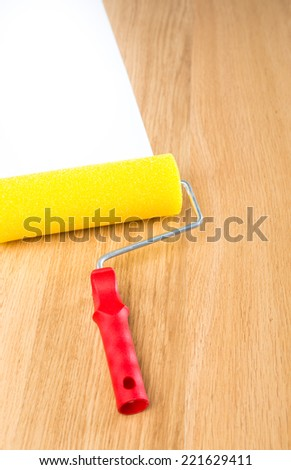 Yellow and red paint roller on hardwood floor with white copyspace paint. - stock photo