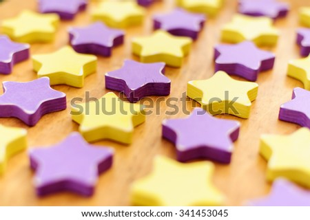 yellow and violet wooden distressed stars on wooden background - stock photo