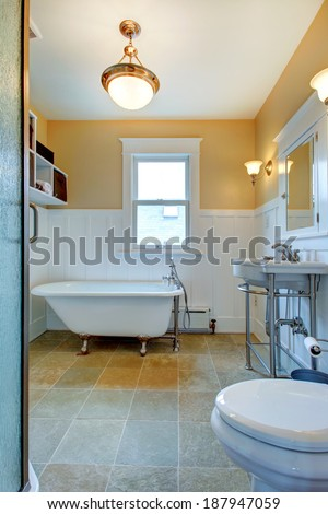 Yellow and white bathroom with window, washbasin stand and claw foot tub. - stock photo