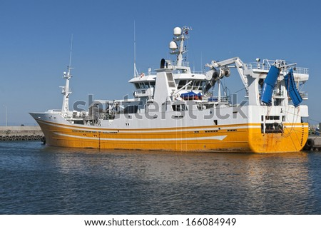 Yellow and White fishing vessel at port in Hirtshals, Denmark - stock photo