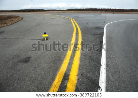 Yellow and white markings of a small airfield taxiway. - stock photo