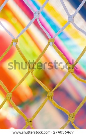 Yellow and white net and very colorful background in children playground - stock photo