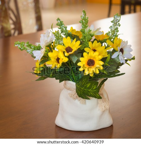 Yellow and white plastic flowers in white vase on yellow background.Background floral . Pastel style. Selective focus.