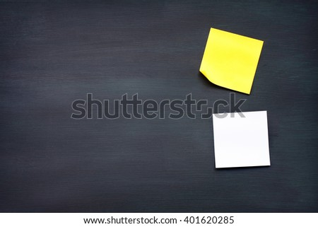 yellow and white reminder sticky note on black board.(blank post it note) flat lat.  - stock photo