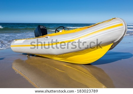 Yellow and white rubber duck inflatable boat on the sandy beach