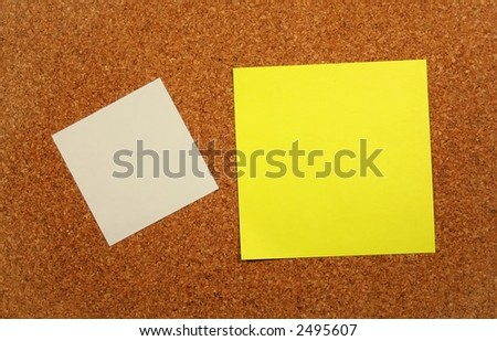 Yellow and white sticky notes on a corkboard.
