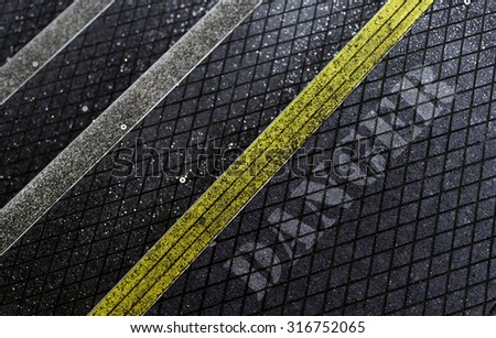 Yellow and white stripped anti-slip pedestrian steps with diagonal patterns providing safety and protection for workers with Danger text  - stock photo