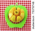 Yellow apple cut by a green tool over white and red cloth - stock photo