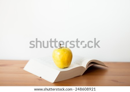 yellow apple on a open book - stock photo