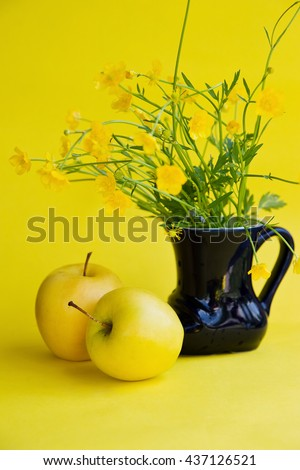 Yellow apples and bouquet of yellow wild flowers in a dark blue vase on a yellow background.