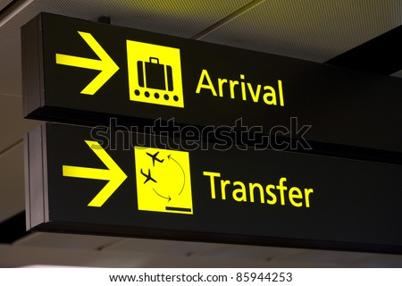 yellow arrivals & transfer sign at a international airport - stock photo