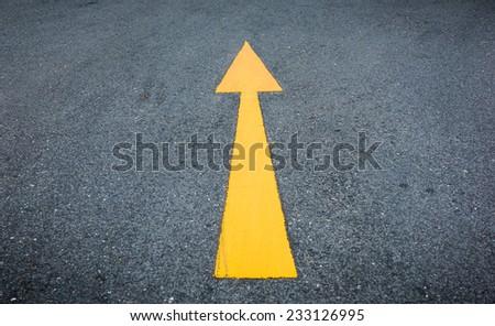 yellow arrow on the road - stock photo