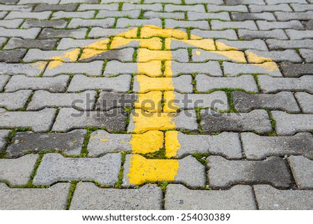 Yellow arrow painted on gray cobblestone pavement, road direction sign - stock photo