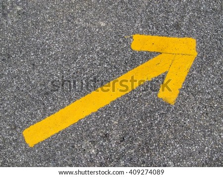 yellow arrow sign or symbol on the asphalt background  texture - stock photo