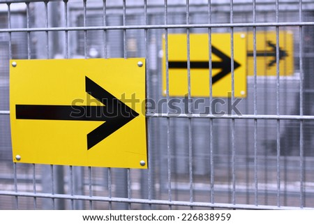 yellow arrow signs on fence - stock photo
