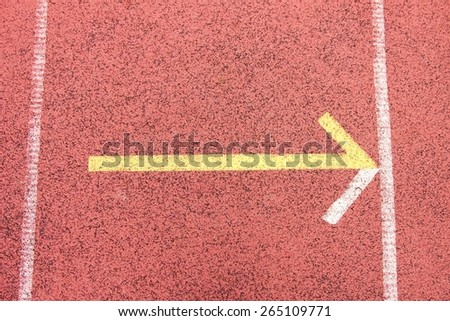 Yellow arrow, white lines and texture of outdoor  running racetrack, red rubber racetracks in small stadium. - stock photo