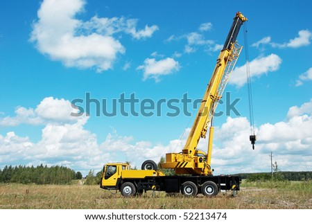 yellow automobile crane with rise n telescopic boom outdoors over blue sky - stock photo
