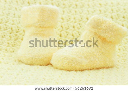 Yellow baby booties and blanket with room for text. - stock photo