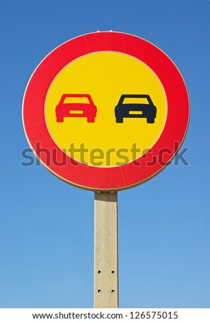 Yellow background No overtaking signal in a road - stock photo