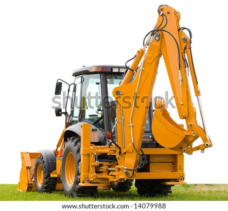 yellow backhoe on green grass - stock photo