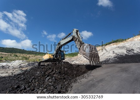 yellow backhoe work in coalmine - stock photo