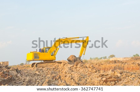 Yellow backhoe working digging for the construction of reservoirs in rural areas. - stock photo