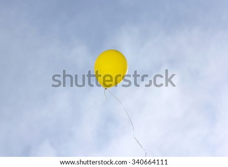 Yellow balloon flying on a blue sky background. - stock photo