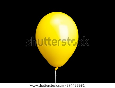 Yellow balloon on white ribbon isolated on black background