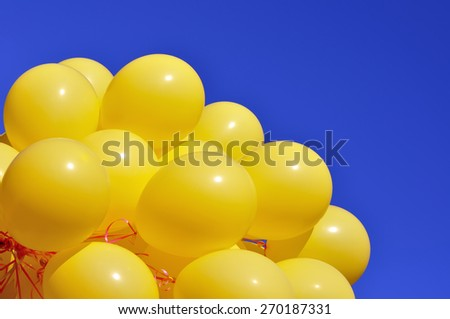 yellow balloons in the city festival on blue sky background - stock photo