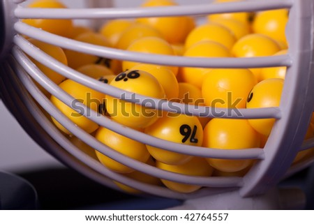 Yellow balls in a basket used for random selection. - stock photo