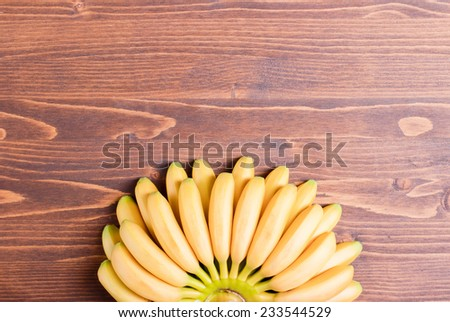 yellow bananas baby tips down below fan on top of the brown board with space for text - stock photo