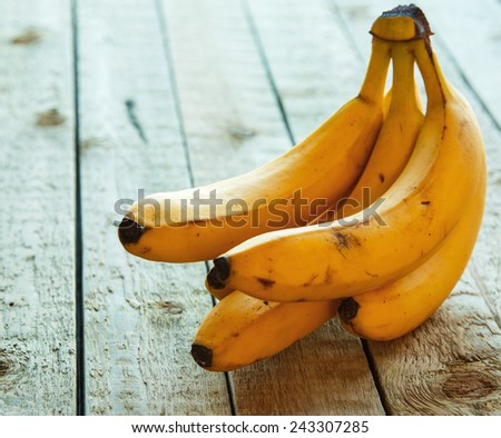 Yellow bananas on woodent table - stock photo