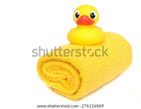 Yellow bath rubber duck on a yellow towel isolated on white  - stock photo
