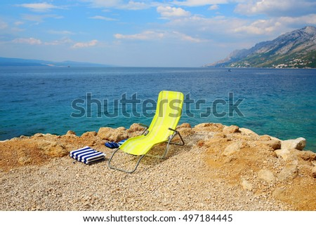 Yellow beach chair empty chaise lounge on rocky shore on sunny summer day on beautiful blue sea and sky
