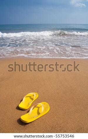 Yellow beach slippers on sandy beach, summer, bathing - stock photo