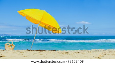 Yellow beach umbrella on the tropical beach - stock photo