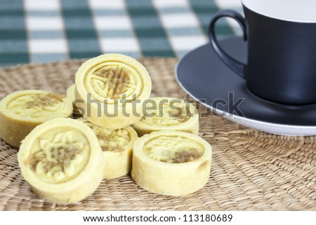 Yellow bean cake on a bamboo mat with a black cup of tea.