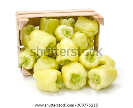 Yellow bell peppers spilled out from wooden crate. Capsicum annuum - stock photo