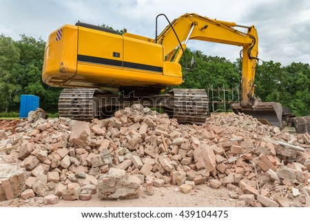 Yellow belt excavator on heap of bricks of demolished house - stock photo