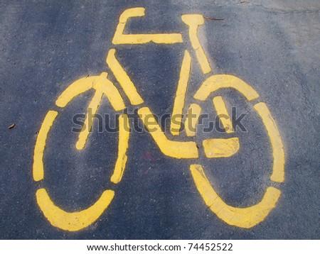 Yellow bicycle sign on asphalt - stock photo
