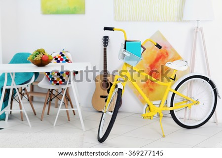 Yellow bicycle with books in light living room interior - stock photo