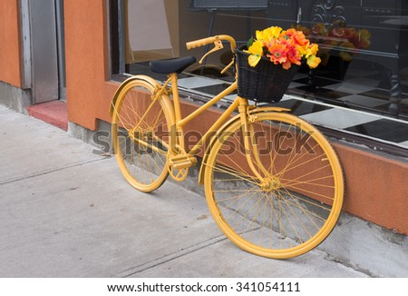 Yellow bicycle with flowers - stock photo