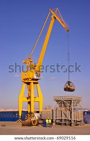 Yellow big crane on a dock unloading a cargo Ship - stock photo