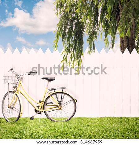 yellow bike in front of a white fence - stock photo