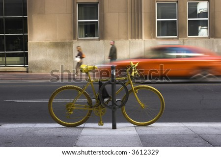 Yellow bike locked up to a post with the world passing by.